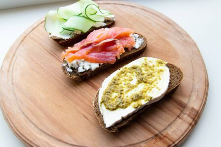 Food and proper nutrition concept. Tasty fresh sandwich with red fish, feta cheese cucumber and pesto on a pink ceramic plate on a wooden board Stok Fotoğraf