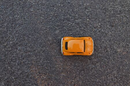 Minimal creative concept. Top view shot of orange toy car on a black background
