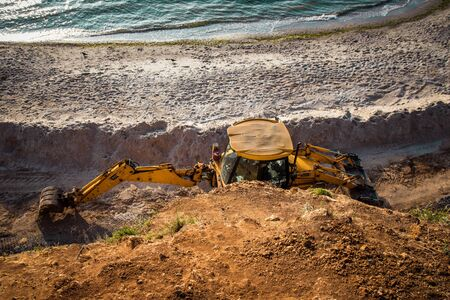 Tractor on a sandy beach, cleaning, after the winter, preparation for the holiday season. Stok Fotoğraf