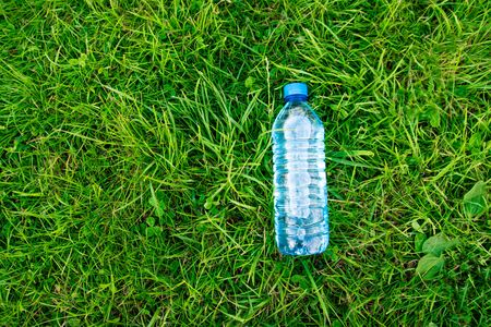 Top view composition of bottle of clean drinking water on a grass background with place for text