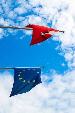 The flag of Denmark and the European Union against a blue sky develops in the wind