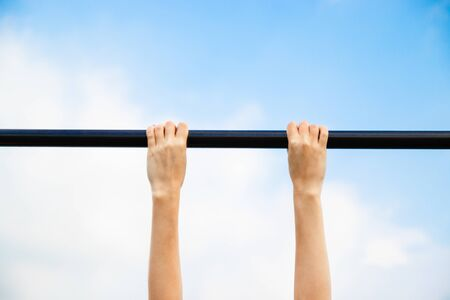 Female hands hold on to horizontal bar against blue sky. Young girl passes the standards for pulling up on a horizontal bar in the park sunny day.