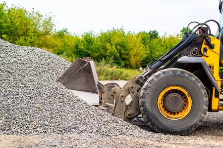 Yellow wheel loader bulldozer is working in quarry against the background of crushed stone storage. Stock fotó