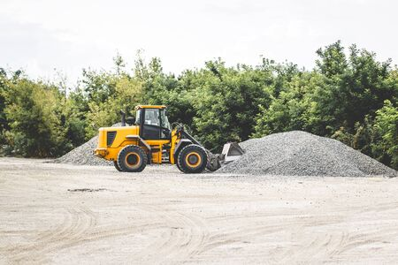 Tractor loads crushed stone in the production of concrete.