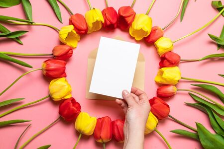 International Women's Day, mother's day greeting concept. Composition of fresh flowers, a bouquet of red tulips, paper texture background with envelope. Foto de archivo