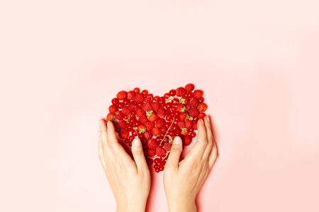 Female hands and red berries in the shape of a heart on a pink background. Health diet heart abstract concept Imagens