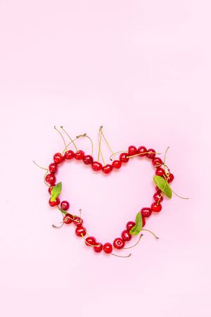 Vertical photo for blog or story. Red cherry berries in the shape of a heart on a pink background. Flat lay. Food concept.