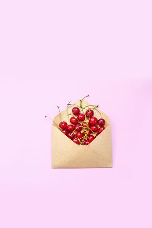 Food concept. Envelope with ripe red cherry berries on a pink background. Invitation card, flat lay.