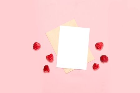 An empty envelope with a sheet on a pink background, decorated with native raspberries Stockfoto