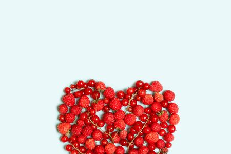 Heart shape assorted berry fruits on blue background. Summer banner concept