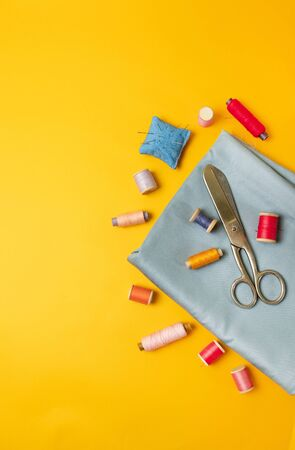 Sewing accessories on a colored yellow background top view. Фото со стока
