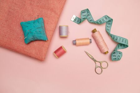 Sewing accessories and fabric on a pink background. Tailoring and craft concept.