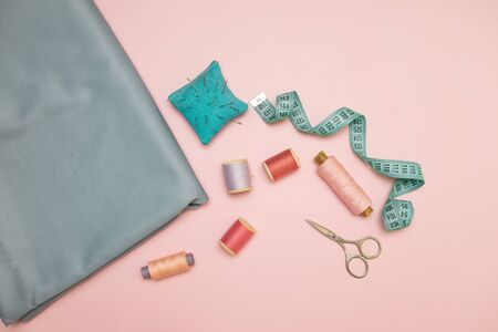 Needlework tools, blue knitted needlepoint for sewing, scissors and colored spools of thread on a pink background with copy space for text