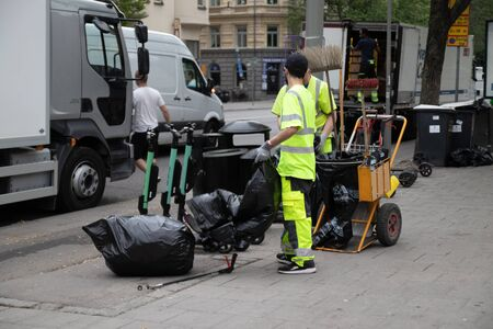 Stockholm, Sweden June 7 2019: Caring for ecology concept. Garbage sorting. Garbage collection worker putting bin into waste truck. For removal