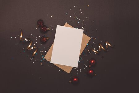 Empty card in kraft envelope on dark background decorated with confetti and red balls. Holiday and invitation mockup.