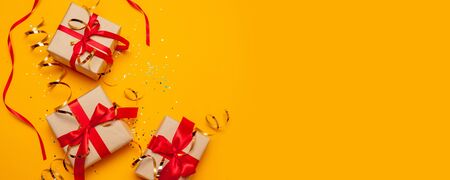 Christmas banner. Xmas background design, with realistic craft gift box with red ribbon and glitter confetti on a yellow background Stock Photo