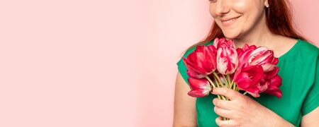 Girl with pink peonies bouquet at pink wall. Women's hands are holding a bouquet of tulips Stock Photo - 130912181