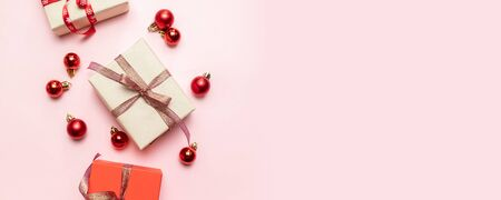 Christmas composition with red present box, ribbons, red big and small balls, holiday decorations on pink background. Creative flat lay, top view design Stock Photo