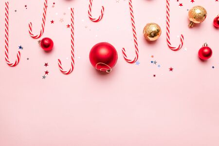 New Year Christmas Background with Candy Canes, gold and red balls on pink background. Flat lay, top view, copy space