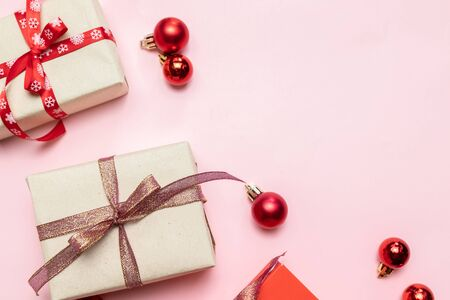 Christmas composition with red present box, ribbons, red gold big and small balls, holiday decorations on pink background. Flat lay, top view, copy space Stock Photo - 131216824