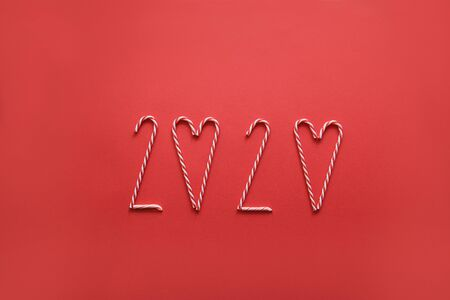 2020 number made with various Christmas cone candy on red background. Heart background made of candy sticks Stock Photo