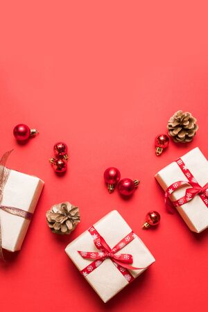 Christmas composition with red present box, ribbons, red big and small balls, brown cones holiday decorations on a red background. Minimal christmas concept.