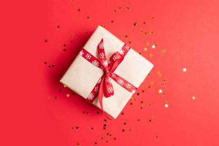 Gift box with gold stars decoration on red background. Minimal concept for birthday, mother day or wedding.