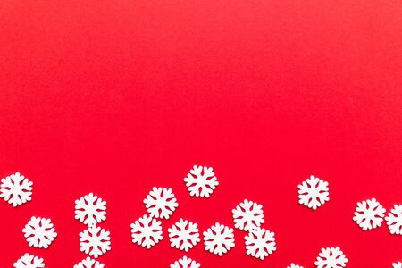 Christmas New Year design concept with white snowflakes on a red background. Flat lay, top view, copy space