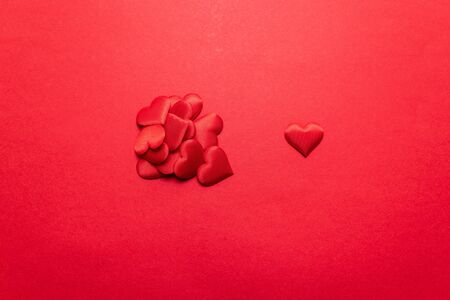 Valentines day concept. Search for a love partner or loved one. Red hearts on a red background. Flat lay, top view, copy space