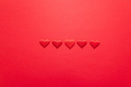Valentine day background with red hearts on a red background. Flat lay, top view, copy space Stock Photo - 131239794