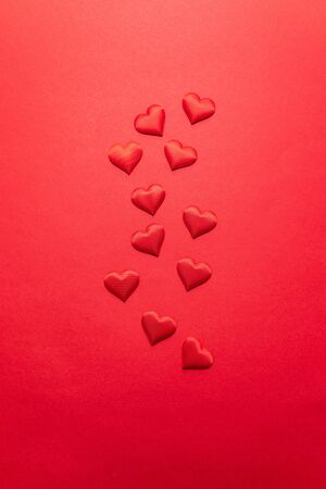 Valentines day concept. Red hearts on a red background. Flat lay, top view, copy space