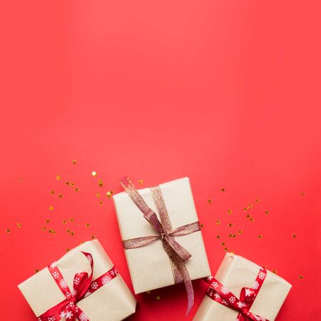 Creative composition with red present box, ribbons, red gold holiday decorations on red background. Creative composition for birthday, Christmas, New Year Stock Photo - 131307122