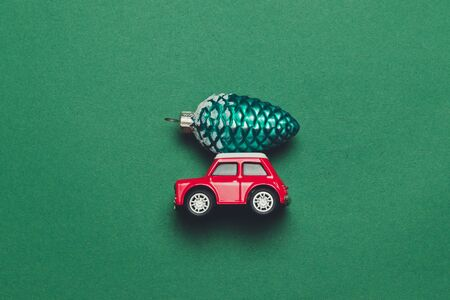 Creative concept of red toy car model with Christmas toy on a car hood on a green background Banque d'images