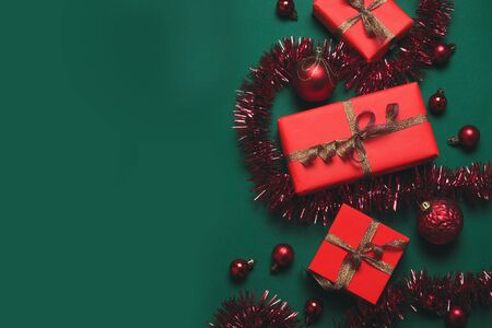 Creative composition with gifts or presents boxes with red bows, red balls on green background. Flat lay style composition, top view.