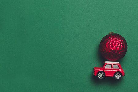 Concept créatif de voiture jouet rétro rouge avec livraison pour Noël ou nouvel an jouet boule de Noël sur fond vert. Mise à plat, vue de dessus, espace de copie Banque d'images