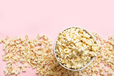 Creative food background with popcorn on pink background. Unhealthy diet concept.