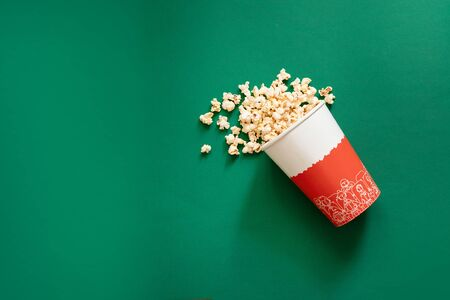 Top view of popcorn in paper bag on green background top view copy space. Unhealthy diet concept. Stock Photo - 131475802