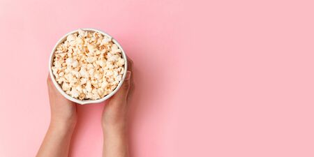 Top view of tasty popcorn in in paper box for cinema. Flat lay style composition, top view.