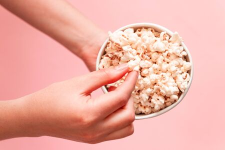 Woman eating popcorn. Popcorn in paper bag on pink background
