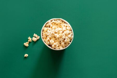 Top view of popcorn in paper bag on green background top view copy space. Unhealthy diet concept.