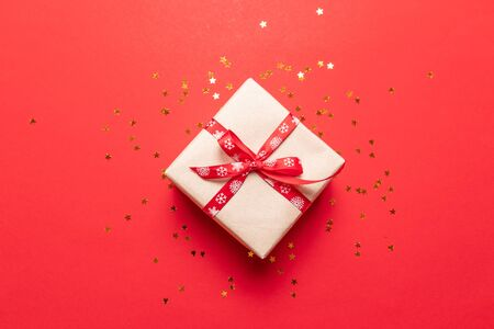 Creative composition of gift box with gold decoration bow on red background. Minimal New Year concept.