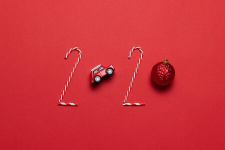 Christmas and New Year holiday 2020 inscription from various decorated objects classic red glass baubles ball, toy car on a red background. Flat lay, top view