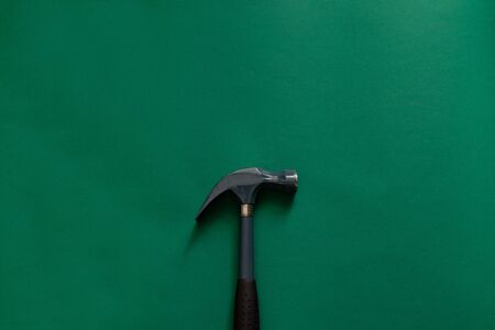 Claw hammer and nail for construction isolated on green background. Working tool for repair in the apartment and at home Banco de Imagens