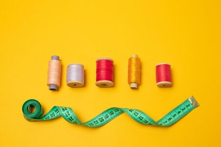 Composition with threads and sewing accessories on a yellow background. Top view, flat lay. Copy space for text.