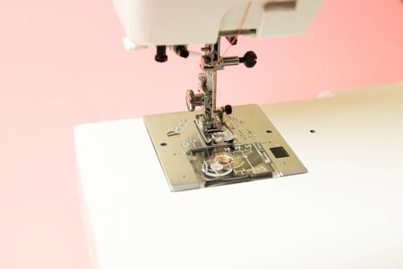 Close-up of a sewing machine on a pink background. Preparation for the production process. Can be used for article, web banner or poster. Imagens