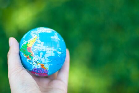 World environment day concept. Attractive ecological problem positive poster. Human hands holding earth globe on blurred green background