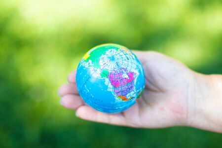 World environment day or saving world Ecology concept. Human hands holding earth globe on blurred green background Banco de Imagens