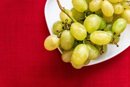 Big tasty sweet grapes on white plate on a red background Banco de Imagens