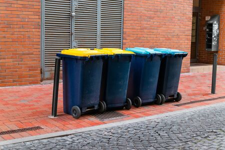 Various plastic garbage containers with colored lids for environmentally friendly sorting of garbage or for recycling with full plastic bags for trash, plastic, glass, paper and metal wastes. Ecological concept