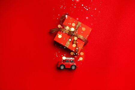 Minimal creative holiday and travel concept of red toy car toy with a gift on the trunk, blurry glitter on a red background